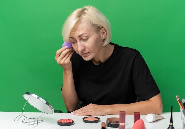 Patrząc w lustro młoda piękna dziewczyna siedzi przy stole z narzędziami do makijażu, nakładającymi krem tonujący z gąbką odizolowaną na zielonej ścianie