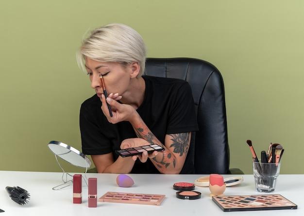 Patrząc w lustro młoda piękna dziewczyna siedzi przy stole z narzędziami do makijażu, stosując cień do powiek za pomocą pędzli do makijażu na oliwkowo-zielonej ścianie