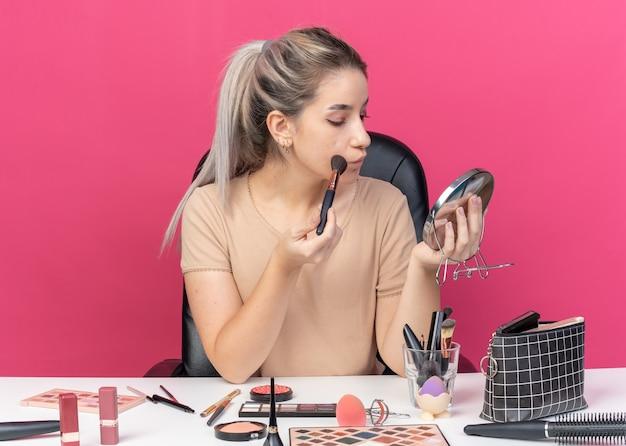 Patrząc w lustro młoda piękna dziewczyna siedzi przy stole z narzędziami do makijażu, stosując róż w proszku na różowej ścianie