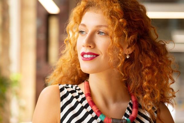 Patrząc w okno. kręcona rudowłosa kobieta w naszyjniku patrząca przez okno
