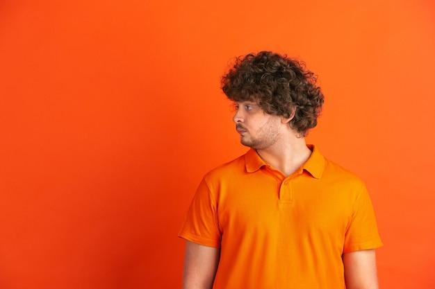 Patrząc z boku. kaukaski monochromatyczny portret młodego człowieka na pomarańczowej ścianie. piękny męski model kręcony w stylu casual.