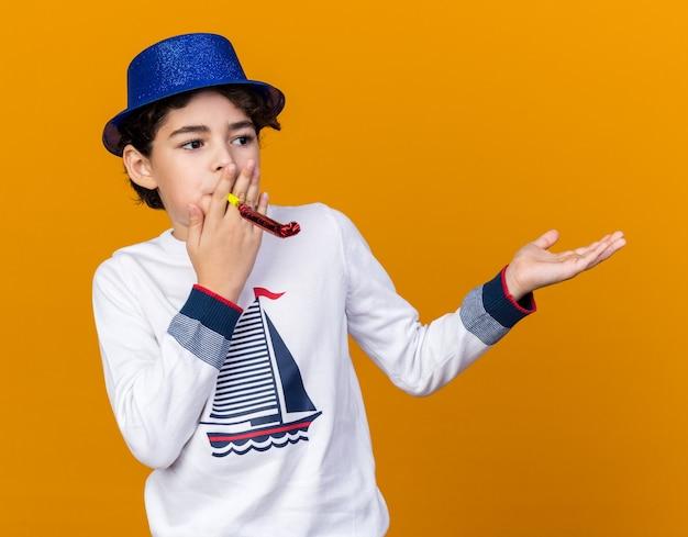 Patrząc z boku mały chłopiec ubrany w niebieską czapkę imprezową dmuchający punkty gwizdka ręką z boku na białym tle na pomarańczowej ścianie