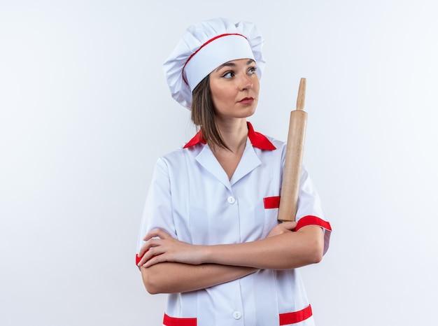 Patrząc z boku młoda kobieta kucharz ubrana w mundur szefa kuchni trzymająca wałek do ciasta krzyżujący ręce izolowane na białej ścianie