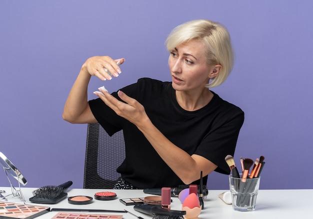 Patrząc z boku młoda piękna dziewczyna siedzi przy stole z narzędziami do makijażu, trzymając krem do włosów na niebieskiej ścianie