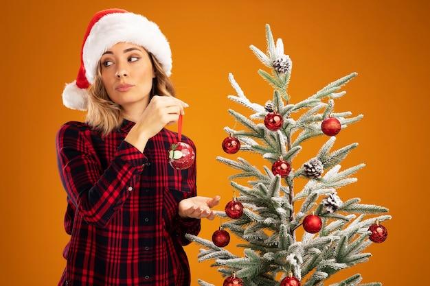 Patrząc z boku młoda piękna dziewczyna stojąca w pobliżu choinki w świątecznym kapeluszu udekorować choinkę udekorować drzewo na białym tle na pomarańczowym tle
