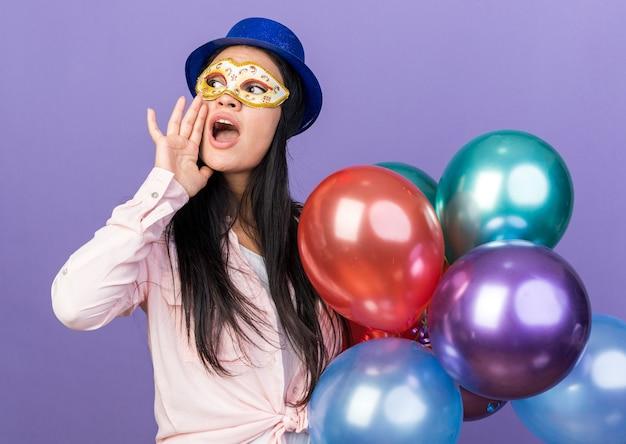 Patrząc z boku młoda piękna kobieta nosząca imprezowy kapelusz i maskę na oczy, trzymająca balony, wołająca kogoś odizolowanego na niebieskiej ścianie