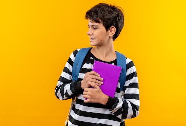 Patrząc z boku młody szkolny chłopiec nosi plecak, trzymając książkę