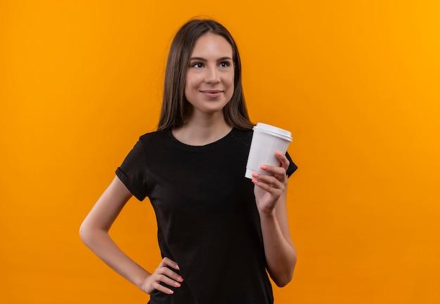 Patrząc z boku, zadowolona młoda dziewczyna kaukaska ubrana w czarny t-shirt z filiżanką kawy położyła rękę na biodrze na odizolowanej pomarańczowej ścianie