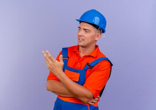 Patrząc z boku, zadowolony młody konstruktor w mundurze i hełmie ochronnym wskazuje na ręce z boku