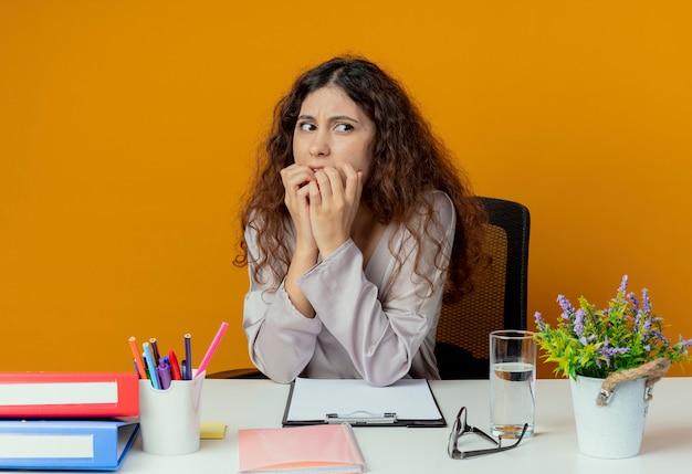 Patrząc z boku zaniepokojony młoda ładna kobieta pracownica biurowa siedzi przy biurku z narzędzi biurowych gryzie paznokcie na pomarańczowej ścianie