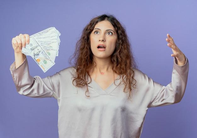 Patrząc z boku, zdziwiona młoda ładna dziewczyna trzyma pieniądze i rozkłada ręce na białym tle na niebieskiej ścianie
