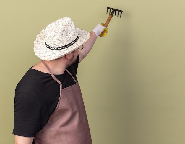 Patrząc za młodego ogrodnika płci męskiej w kapeluszu ogrodniczym i rękawiczkach, trzymającego prowizję za odizolowaną na oliwkowozielonej ścianie z miejscem na kopię