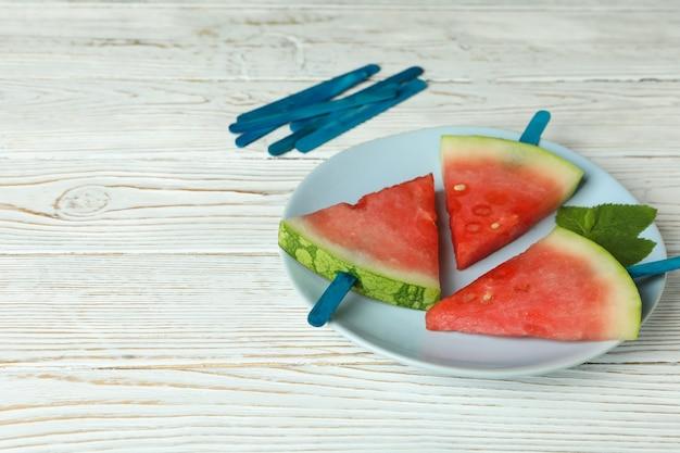 Patyczki lodu z kawałkami arbuza na talerzu na białym drewnianym stole