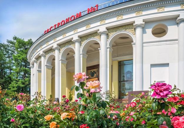 Pawilon gastronomiczny z kolumnami na terenie wogn-u w moskwie w letni dzień. podpis: delikatesy nr 1