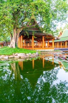Pawilon w stylu tajskim z jeziorem i drzewem w ogrodzie