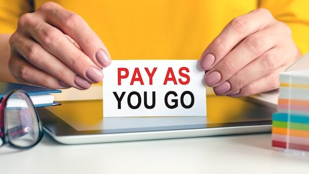 Pay as you go jest napisane na białej wizytówce w rękach kobiety