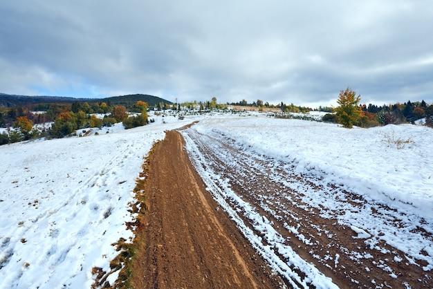 Październik karpaty z pierwszym zimowym śniegiem na brudnej drodze