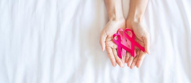 Październik miesiąc świadomości raka piersi, dorosły kobieta ręka trzyma różową wstążkę na różowym tle do wspierania ludzi żyjących i chorych. koncepcja międzynarodowego dnia raka kobiet, matki i świata