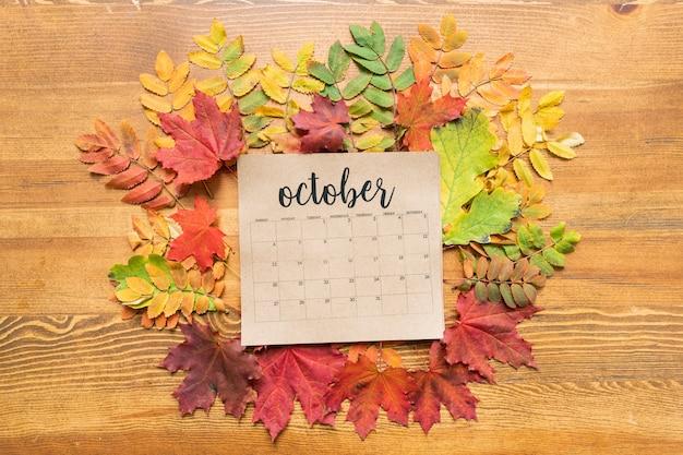 Październikowy arkusz kalendarza na drewnianym stole wśród czerwonych, zielonych i żółtych liści jesienią