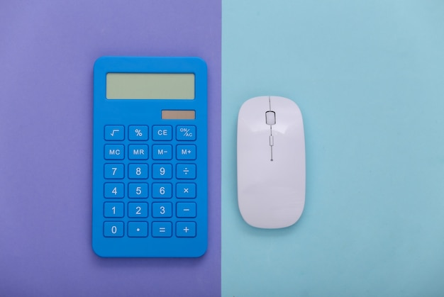 Pc mysz z kalkulatorem na fioletowym niebieskim tle. widok z góry