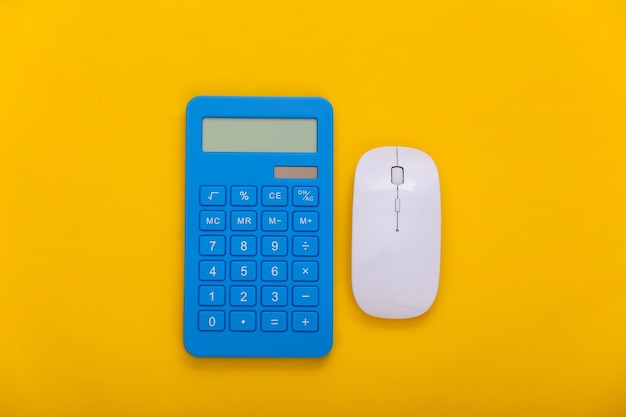 Pc mysz z kalkulatorem na żółtym tle. widok z góry