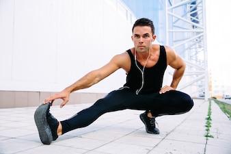 Pełny długość widok atlety samiec robi rozciąganiu ćwiczy dla ciała, słucha muzyka