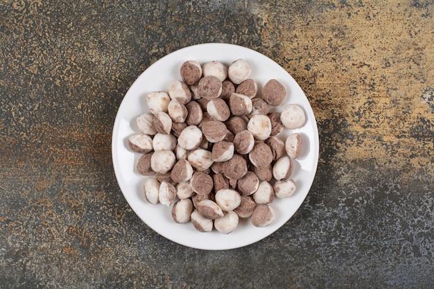 Pęczek brązowych cukierków na białym talerzu.