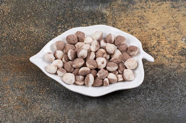 Pęczek brązowych cukierków na talerzu w kształcie liścia.