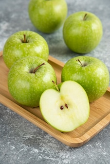 Pęczek całych i pokrojonych zielonych jabłek na drewnianym talerzu.