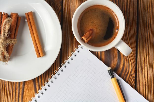 Pęczek cynamonu z sznurkiem, filiżanka kawy i notatnik