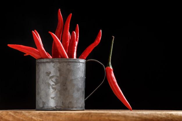 Pęczek czerwonej papryki w metalowej filiżance na czarnym tle. koncepcja kulinarna. ostra przyprawa. zbliżenie.