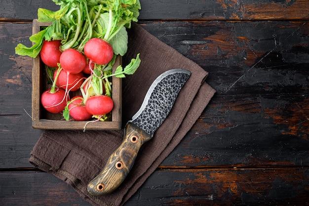 Pęczek czerwonej rzodkwi z zestawem zielonych liści, na starym ciemnym tle drewnianego stołu, widok z góry płasko leżący, z miejscem na kopię tekstu