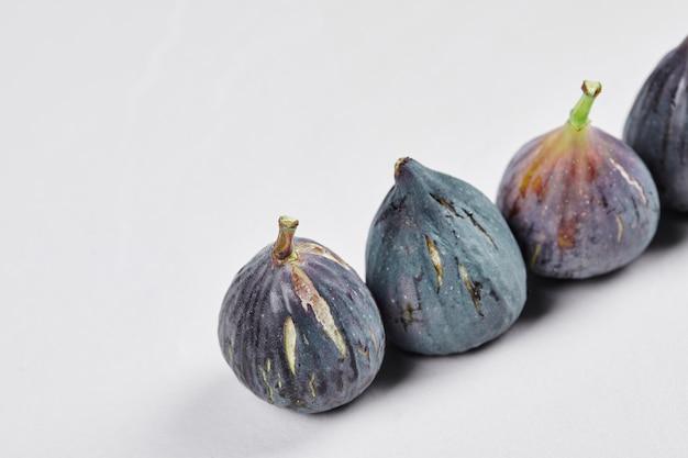 Pęczek dojrzałych fig na białym tle.