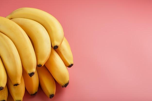 Pęczek dojrzałych żółtych bananów na różowym tle. widok z góry. minimalistyczna koncepcja. wolna przestrzeń
