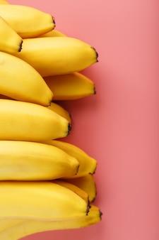 Pęczek dojrzałych żółtych bananów na różowym tle.