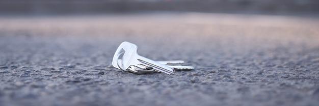 Pęczek kluczy leży na drodze w koncepcji usługi odzyskiwania kluczy parkingowych