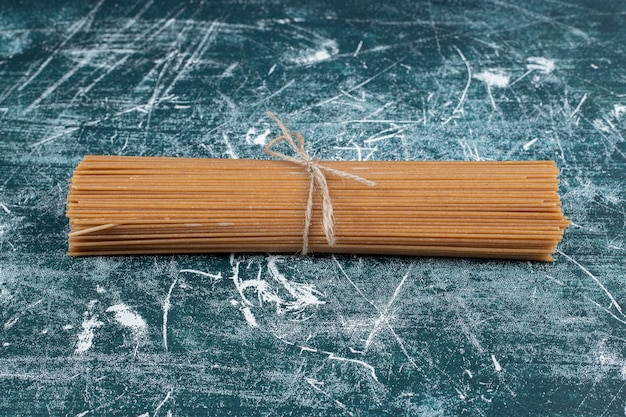 Pęczek makaronu pełnoziarnistego spaghetti związany liną na marmurowej przestrzeni.