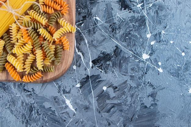 Pęczek niegotowanego spaghetti w linie z wielobarwnym makaronem na marmurowym tle.