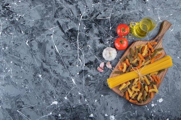 Pęczek niegotowanego spaghetti w sznurku z wielobarwnym makaronem i warzywami.