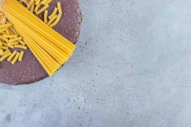 Pęczek niegotowanego spaghetti w sznurze ze świeżymi czerwonymi pomidorami i czosnkiem.