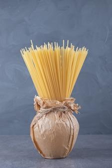 Pęczek niegotowanego suchego spaghetti w wazonie.