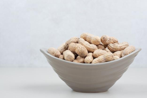 Pęczek organicznych orzeszków ziemnych w ceramicznej misce