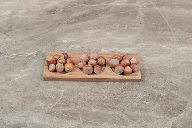 Pęczek orzechów laskowych w drewnianej tablicy na tle marmuru. wysokiej jakości zdjęcie