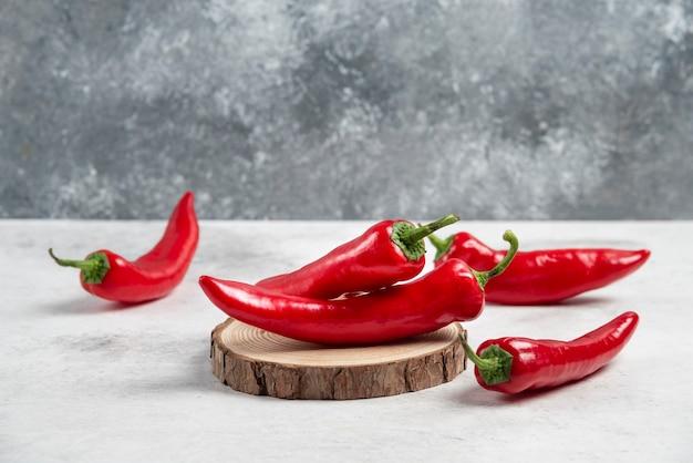 Pęczek ostrej papryki chili na kawałku drewna.
