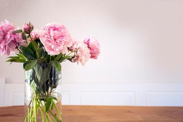 Pęczek pastelowej różowej piwonii z zielonymi liśćmi w szklanym wazonie na drewnianym stole w pobliżu białej ściany
