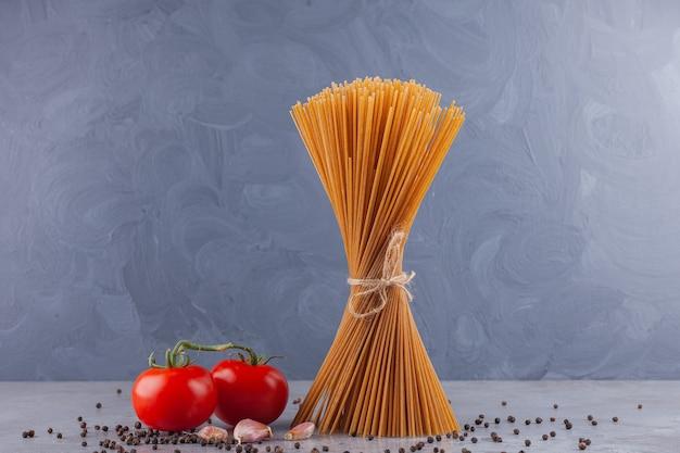 Pęczek pełnoziarnistego spaghetti zawiązany sznurkiem i świeżymi czerwonymi pomidorami.