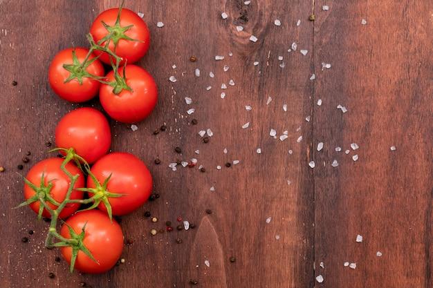 Pęczek pomidora na drewnianej fakturze z rozrzuconą solą