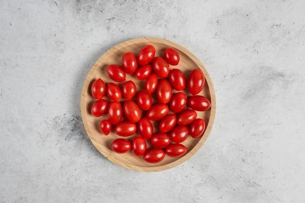 Pęczek pomidorków koktajlowych na drewnianym talerzu.