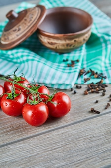 Pęczek pomidorów z gałęzi i pustą miskę z goździkami na drewnianym stole