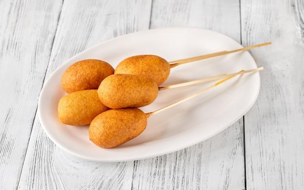 Pęczek psów mini kukurydzy na białym talerzu porcji
